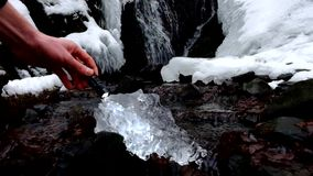 Hand with strong flash light shinning into beautiful big piece of ice with abstract cracks. Fallen icicle bellow waterfall stock footage