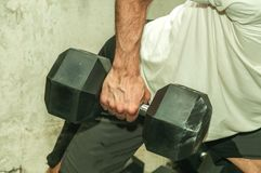 Hand of a strong muscular man holding big black heavy dumbbell weight as workout for back muscles in the gym.  royalty free stock images