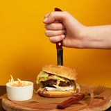 Hand stubbing burger with knife Royalty Free Stock Photo