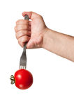 A hand stucking a fork in a red tomato Stock Photos