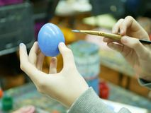 The hand of the student holds a brush with paint for coloring eggs for Easter. Background art school workshop, preparation for the holiday of Easter stock photos