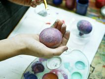 The hand of the student holds a brush with paint for coloring eggs for Easter. Background art school workshop, preparation for the holiday of Easter royalty free stock images
