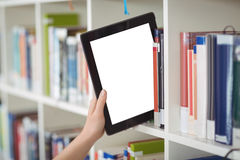 Hand of student keeping digital tablet in bookshelf in library. At school royalty free stock photography