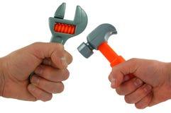 Hand, stuk speelgoed hamer en moersleutel Royalty-vrije Stock Foto's
