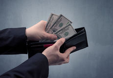 Hand in suit takes out dollar from wallet Stock Photo