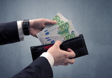 Hand in suit takes out euro from wallet Royalty Free Stock Images