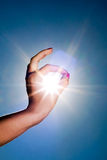 Hand and sun. Woman hand around the sun and blue sky Royalty Free Stock Photography