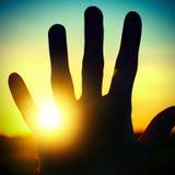 Hand on Sunset Background Stock Photo