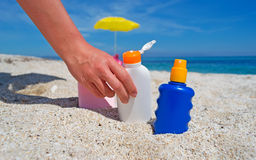 Hand and suntan lotion Stock Photo