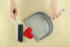 Hand sweeping heart from the floor Royalty Free Stock Photos