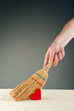 Hand sweeping heart from the floor. With short handled small broom Stock Photos