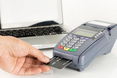 Hand Swiping Credit Card. With Laptop In Background Royalty Free Stock Photography