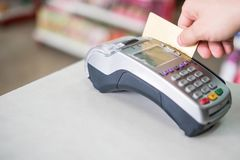Hand swiping credit card on payment terminal in store. Hand swiping credit card on payment terminal in supermarket Royalty Free Stock Photo