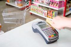Hand swiping credit card on payment terminal in store. Hand swiping credit card on payment terminal in supermarket Royalty Free Stock Images