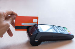 Hand Swiping Credit Card on POS terminal in Store Stock Image
