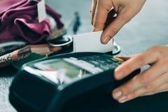 Hand swiping credit card in store. Hand swiping credit card on terminal in store Stock Photos