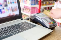 Hand swiping credit card on ternimal and using laptop payment sh. Hand swiping credit card on ternimal and using laptop paying shopping online Stock Photos