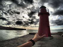 Hand switching on lighthouse at sunset Royalty Free Stock Photo