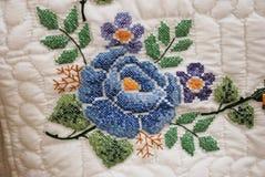 Hand sydd broderad blomma på ett Amish täcke Arkivbilder
