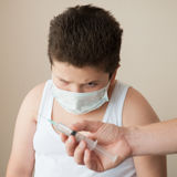 Hand with syringe in front of a fat scared boy in the medical mask Royalty Free Stock Image