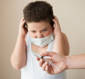 Hand with syringe in front of a thick scared boy in the medical mask Stock Photos