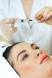 Hand with a syringe over the face Stock Photography