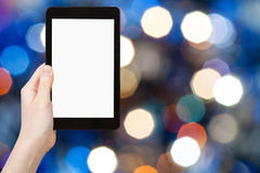 Hand with tablet pc on blurred blue background Stock Photography