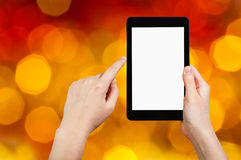 Hand with tablet pc on dark red blurred background Royalty Free Stock Images