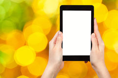 Hand with tablet pc on yellow and green background Stock Images
