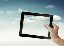 Hand with tablet  in sky. A hand holding a pad in sky show communication Stock Photos