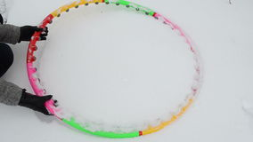 Hand take colorful sport fitness hoop waist from winter snow stock video