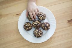 Hand take cookies Chocolate biscuits from plate on wood table.  Stock Photos