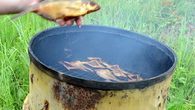 Hand take ecologic smoked fish meal from smokehouse rusty barrel stock video footage