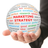 Hand take white ball with red inscription Marketing strategy Stock Photography