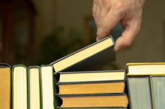 hand takes a book on a shalf in the room or library Stock Images