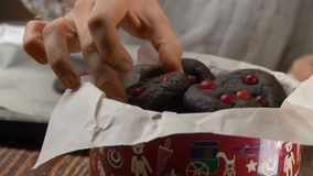 Hand takes chocolate cookies with cranberries from a pan. And puts them in a Christmas box stock footage