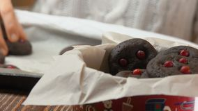 Hand takes chocolate cookies with cranberries from a pan. And puts them in a Christmas box stock video