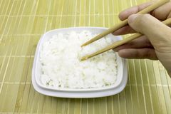 Hand takes cooked rice with chopsticks from a bowl royalty free stock photos