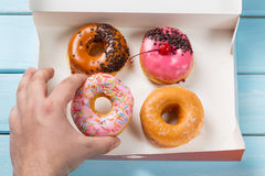 Hand takes donut out of the box with colorful donuts on blue wooden background. Top view.  Stock Photo