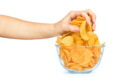 Hand takes a handful of potato chips from a glass bowl Stock Images
