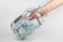 Hand takes out three-liter glass jars thousand Russian rubles Royalty Free Stock Photo