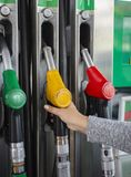 The hand takes the pistol with gasoline or diesel from the refueling column stock photography