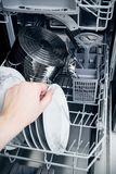 Hand takes plate from dishwasher Stock Image