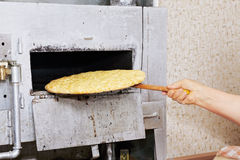 Hand takes prepared bread from oven Stock Image