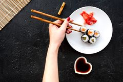 Hand takes sushi roll with salmon and avocado with chopstick. Black background top view royalty free stock photos