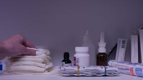 Hand takes a towel from shelf with medicines. Bottles of medicine pills arranged on shelf at drugstore. Hand holding Royalty Free Stock Photos