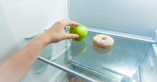 Hand taking apple instead of donut lying in fridge Royalty Free Stock Photo