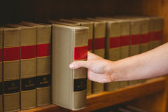 Hand taking a book from bookshelf Royalty Free Stock Photography