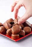 Hand taking chocolate. A woman's hand picking up a chocolate from a red plate against a white background Stock Image