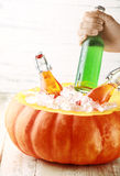Hand Taking Cold Drink from Pumpkin Ice Bucket Stock Photo
